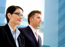 Business people and officebuilding. Young successful business people standing in front of a modern office building, looking away into the future Royalty Free Stock Image