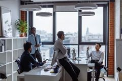 Business people in an open space office with a panoramic window, long shot royalty free stock image