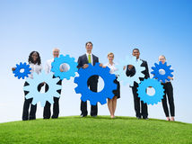 Business People Outdoors Holding Gears Outdoors Stock Photo