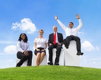 Business People Outdoors Sitting on a Bar Graph Royalty Free Stock Photography