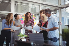 Business people with papers having discussion in creative office Royalty Free Stock Images
