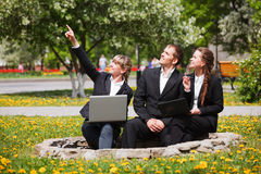 Young business people with laptop in a city park Stock Image