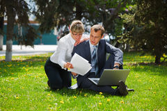Business people in a park. Young business couple in a city park Royalty Free Stock Photography