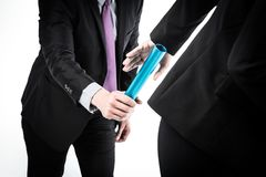 Business People Passing Relay Baton. Studio shot of business people passing relay baton royalty free stock image