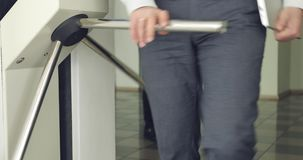 The business people is passing through a turnstile. Solid women and men leave the office through a metal barrier stock footage