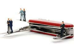 Business people on penknife Stock Image