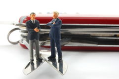 Business people on penknife Stock Photos
