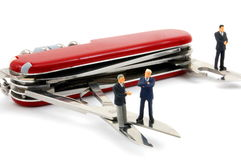 Business people on penknife Royalty Free Stock Photos