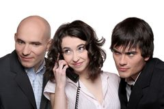 Business people Phone. A young businesswoman holding a telephone receiver surrounded by two businessmen listening Royalty Free Stock Images
