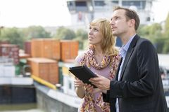 Business people planning. A businesswoman and a businessman  planning with shipping containers in the background Stock Image
