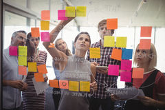 Business people planning with adhesive notes in creative office. Group of business people planning with adhesive notes in creative office royalty free stock image