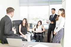 Business People Planning New Strategy In Office. Group of people listening to male colleague sharing ideas during meeting stock image