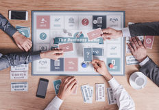 Business people playing a board game Stock Images