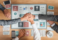 Business people playing a board game. People playing a business board game on a wooden table and stacking hands, cooperation and teamwork concept stock photo