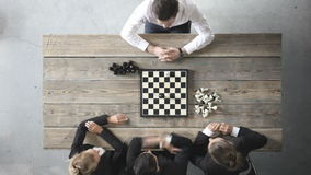 Business people playing chess. Team of workers losing, leader is winning stock video
