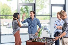 Business people playing table football during break Royalty Free Stock Photos