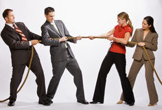 Business people playing tug-of-war. Businessmen and businesswomen in a game of tug-of-war Stock Photography
