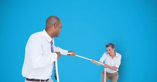 Business people playing tug of war over blue background royalty free stock photos