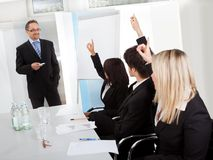Business people at presentation raising hands stock image