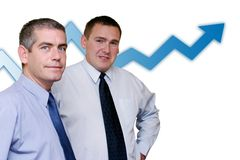 Business people - Profits Growing. Two business people looking on the camera. A climbing blue chart behind them could sugesst success Royalty Free Stock Images