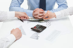 Business people pulling dollars from under director's hands Royalty Free Stock Photography