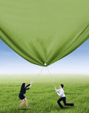 Business people pulling green banner. Two business people is pulling green banner on the meadow Stock Photo