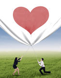 Business people pulling valentine banner Royalty Free Stock Photos