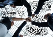Business people putting hands together with black business doodles. Digital composite of Business people putting hands together with black business doodles royalty free stock images
