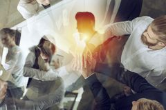 Business people putting their hands together. Concept of startup, integration, teamwork and partnership. Double exposure. Business people putting their hands royalty free stock photo