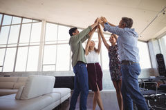 Business people raising hands together at office Stock Image
