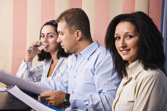 Business people reading in office. Three business people in office at work,man in middle reading some papers,last businesswoman drinking water,focus on first Stock Photos