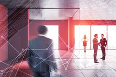 Business people in red office hall. Business people walking and shaking hands in modern office hall with red walls and floor and panoramic windows. Corporate stock photo