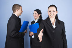 Business people relationships. Business people relationship ,a businesswoman standing in front and saying welcome giving hand and others having a conversation in royalty free stock images