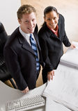 Business people reviewing blueprints together. Two business people reviewing blueprints together Stock Photography