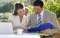 Business people reviewing paperwork at caf? Royalty Free Stock Photography
