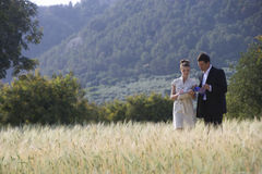 Business people reviewing paperwork in rural field Stock Photography