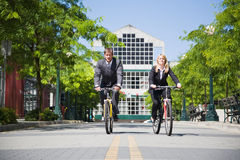Business people riding bicycle. Two business people riding bicycle to work, can be used for gas savings concept stock images