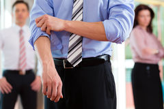 Business and people - roll up the sleeves Stock Image