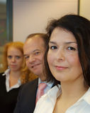 Business people in a row. Three business people in a row, looking at the camera. Focus on woman in front stock photography