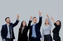 Business people in a row pointing and looking up to copy space Stock Photos