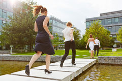 Business people running over a bridge. Many business people running over a bridge in front of the office Stock Image