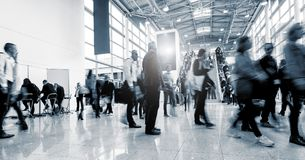 Blurred business people at a International Trade Fair hall. Business people rushing in a lobby of a business center. ideal for websites and magazines layouts stock photos