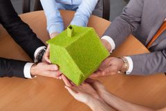Business People's Hand Holding House stock images