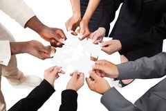 Business people's hands solving jigsaw puzzle. Cropped image of business people's hands solving jigsaw puzzle over white background royalty free stock photos