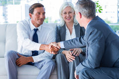 Business people shake hands on couch Royalty Free Stock Images