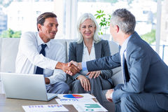 Business people shake hands on couch Stock Images