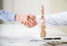 Business people shake hands near built wooden tower Royalty Free Stock Image