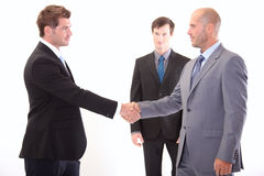 Business people shaking hands. Two businessmen shaking hands in front of their colleague Stock Photos