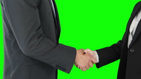 Business people shaking hands. Against green background stock video
