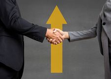 Business people shaking hands against grey background with a yellow arrow. Digital composite of Business people shaking hands against grey background with a Stock Image